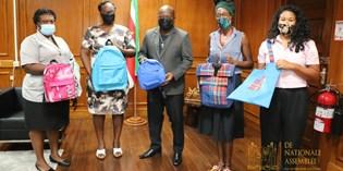 Vrouwelijke ondernemers overhandigen zelf vervaardigde schooltassen aan DNA voorzitter
